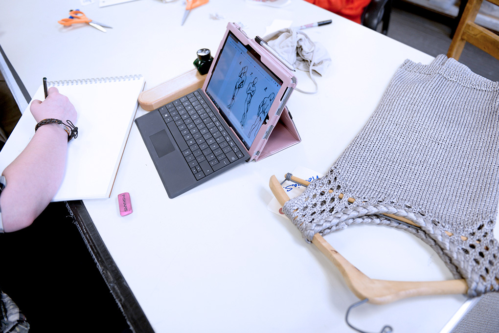 Cornish Costume Design student working with garment, sketch pad, and labtop