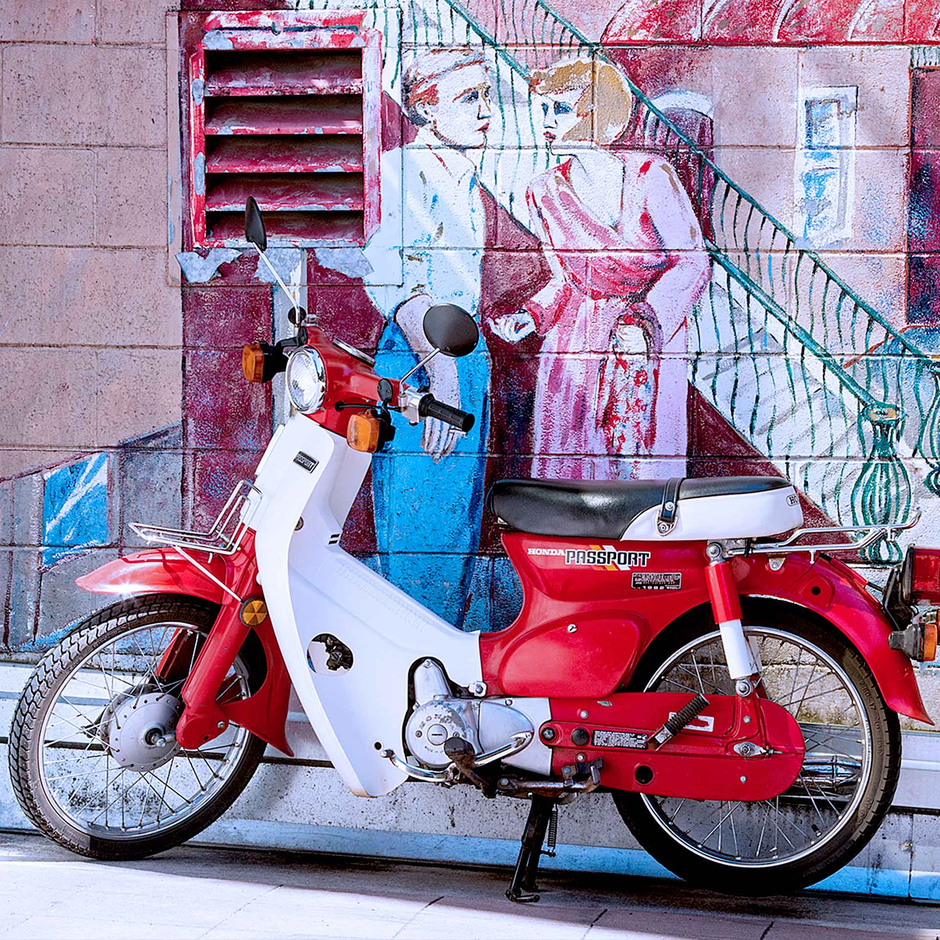 Red moped against colorful mural